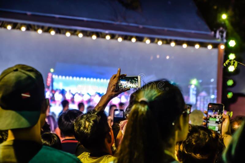 Неясное изображение - люди фотографируют с его смартфоном в представлениях в реальном маштабе времени Pong Lang в ночи на Бангкок стоковые фотографии rf