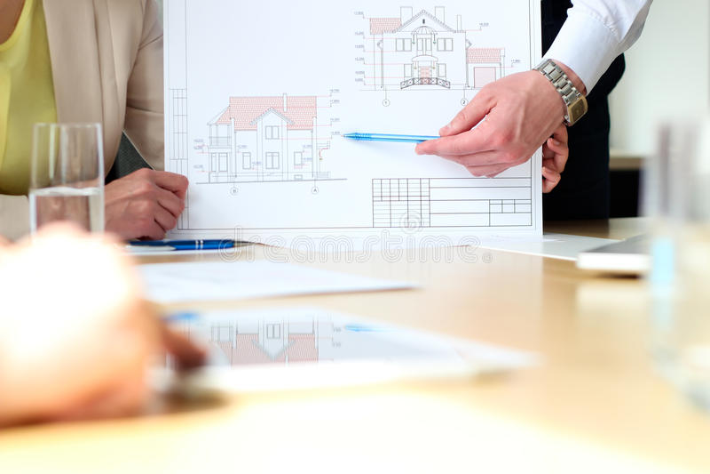 Недвижимый агент показывая дом планирует с бизнесменом стоковое изображение