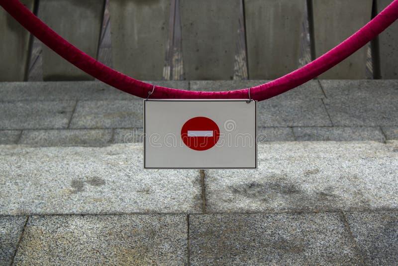 Не впишите знак на красной веревочке против серой предпосылки стоковая фотография rf
