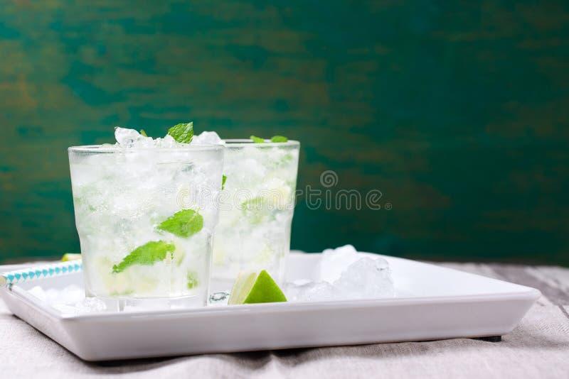 Не коктеиль mojito спирта холодный с свежей известкой, мятой и задавленным льдом на белой плите на винтажной деревянной предпосыл стоковые фото