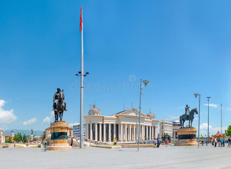 Не определенные туристы посещают центр скопья, квадратную македонию Взгляд каменного подхода к моста, археологического музея и st стоковые фотографии rf