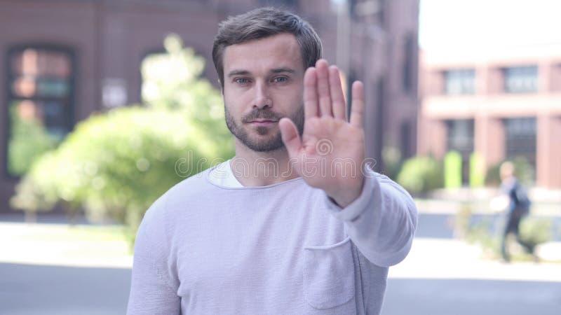 Не позволенный, жест стопа снаружи красивого человека стоящим стоковое фото