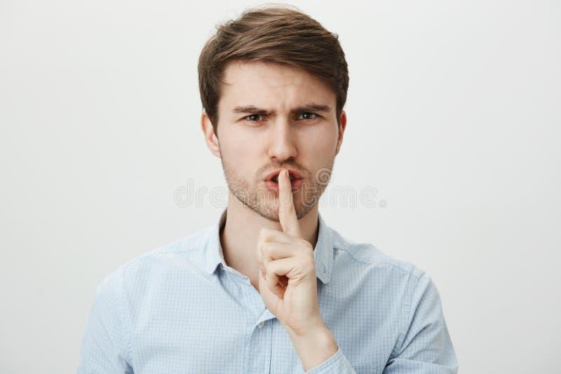 Не причините шум, shh Портрет строгого серьезного красивого парня в вскользь голубой рубашке держа указательный палец над ртом стоковое изображение rf