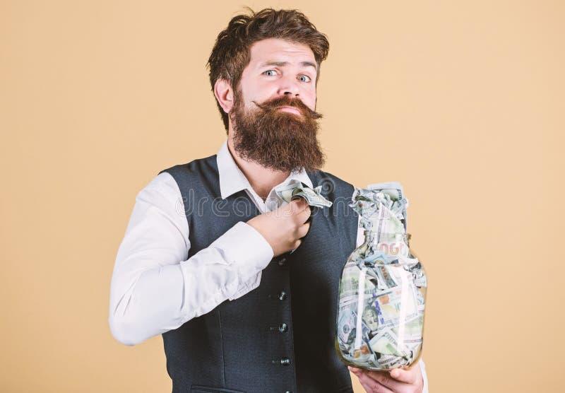Не украдите не чем миллион Бизнесмен крадя бумажные деньги от стеклянного опарника Хипстер пряча американский доллар стоковое изображение