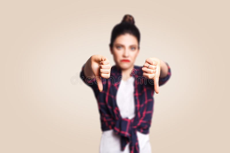нелюбовь Молодая несчастная девушка осадки с непринужденным стилем и волосами плюшки thumbs вниз с ее пальца, на бежевой пустой с стоковое изображение