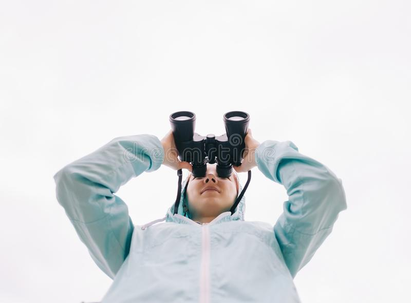 Нижний взгляд женщины путешественника наблюдая с биноклями стоковое изображение rf