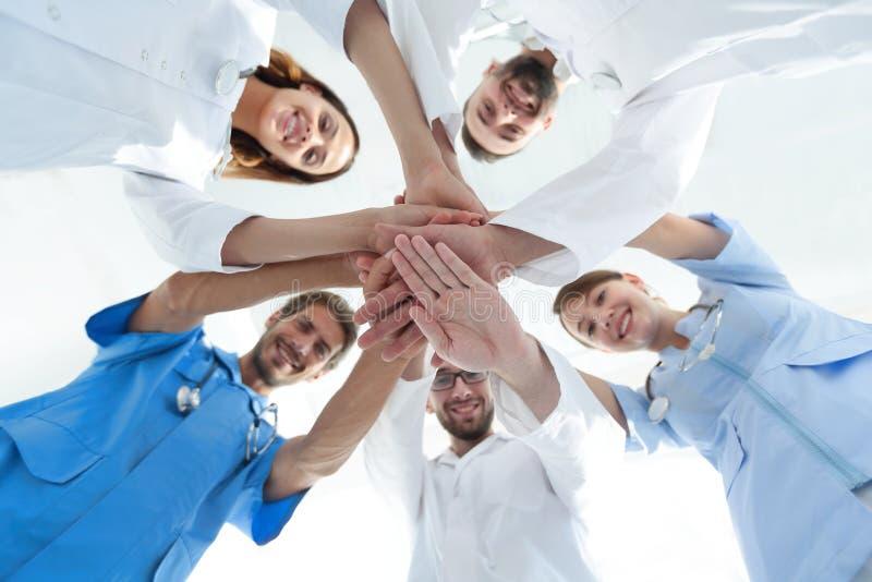 Нижний взгляд команда докторов на медицинском центре сжимала их руки совместно стоковое изображение rf