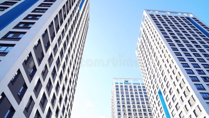 Нижний взгляд новых жилых многоэтажных зданий с голубым небом городская среда Рамка Самые новые жилые комплексы стоковые фотографии rf