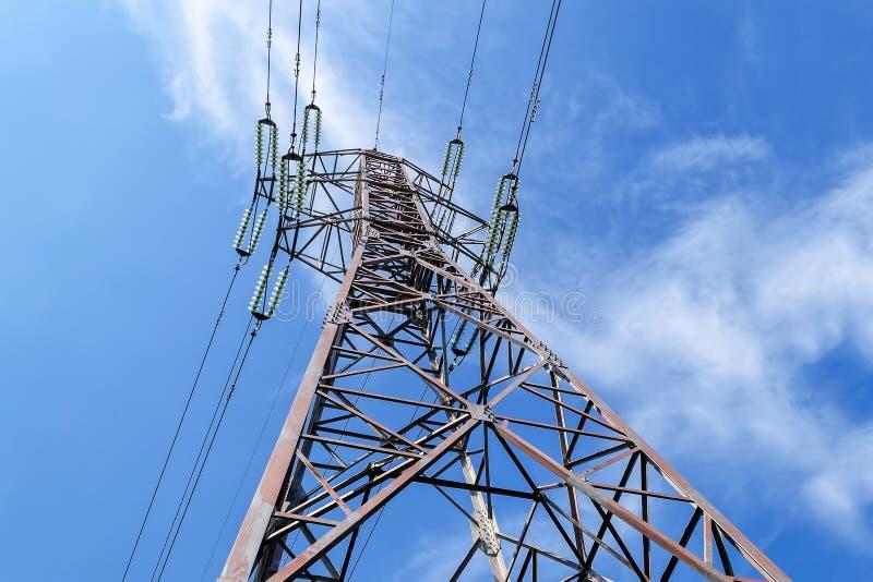 Нижний взгляд опоры силы и высоковольтных проводов со стеклянными взрывателями против яркого голубого неба с белыми облаками на с стоковые фото