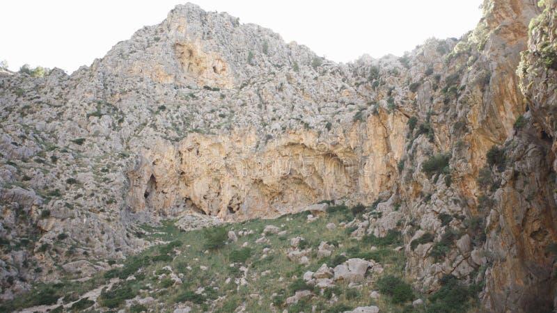 Нижний взгляд скалы на предпосылке неба r Окруженный скалистой горой с растительностью на ноге и редких кустах дальше стоковое фото