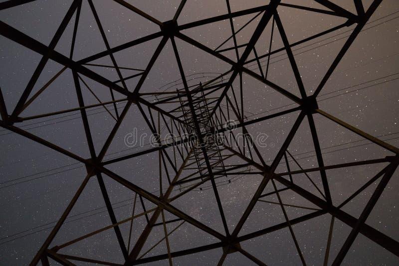 Нижний низкий angled взгляд красивого синего звёздного неба from inside высоковольтной башни стоковые изображения rf
