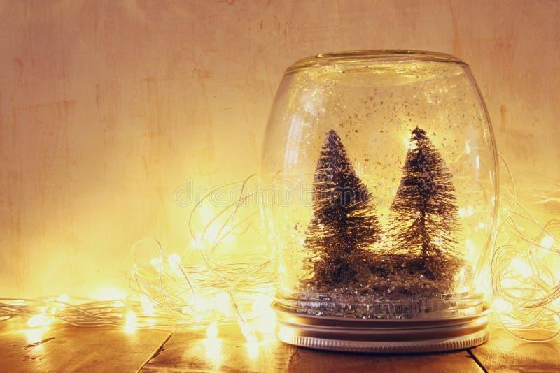 Низкие ключ и год сбора винограда фильтровали изображение рождественских елок в опарнике каменщика с светами гирлянды теплыми и в стоковые фотографии rf