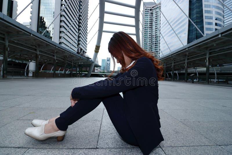 Низкий ключевой портрет усиленных разочарованных молодых азиатских усаживания и чувства бизнес-леди утомлял или разочарование стоковые изображения