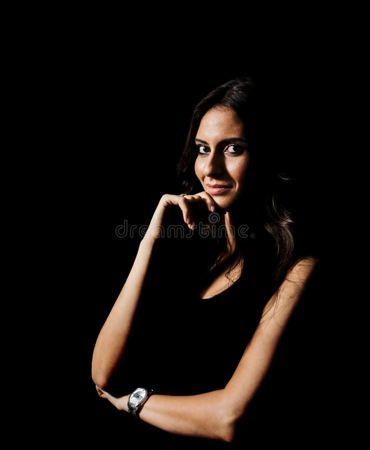 Низкий ключевой портрет молодой испанской женщины смотря камеру стоковое фото rf