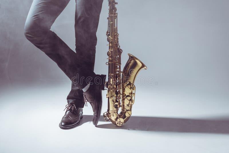 низкий раздел положения профессионального музыканта с саксофоном в дыме стоковые фотографии rf