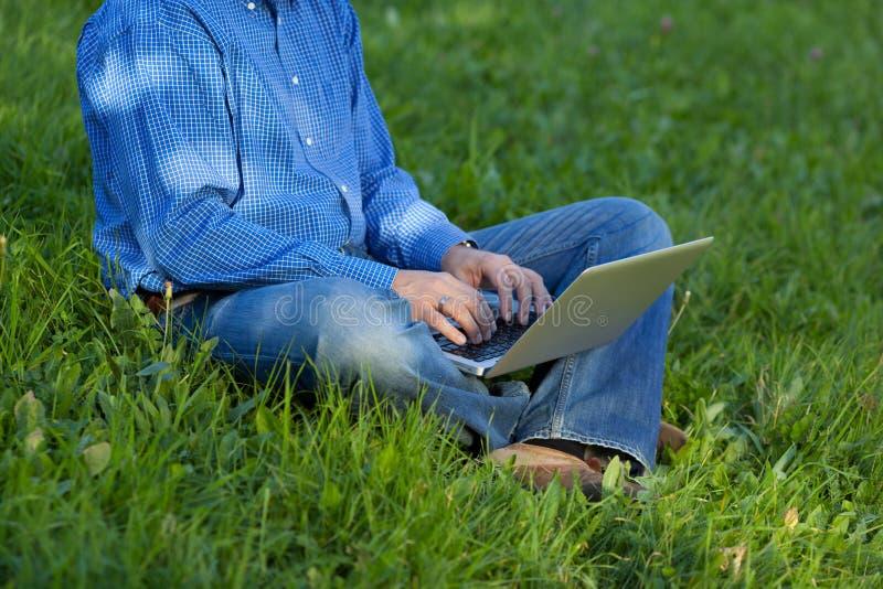 Низкий раздел бизнесмена используя компьтер-книжку пока сидящ на траве стоковые фотографии rf