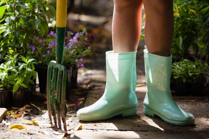 Низкий раздел девушки нося зеленый резиновый ботинок стоя с садовничая вилкой на тропе стоковые фотографии rf