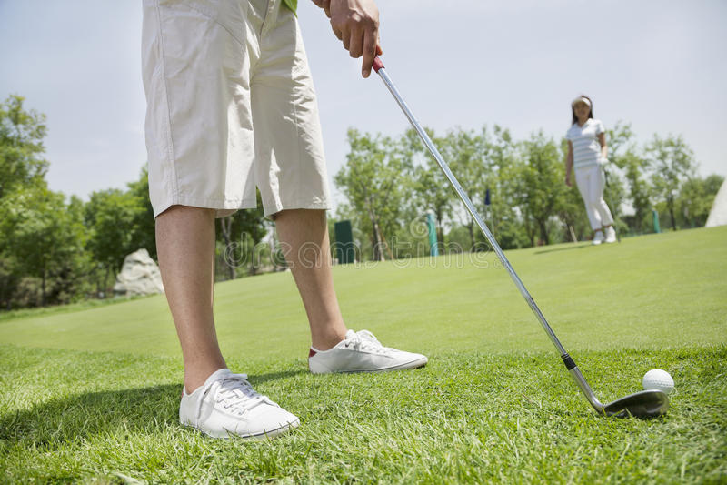 Низкий раздел молодого человека ударяя шарик на поле для гольфа, женщине на заднем плане стоковые фото