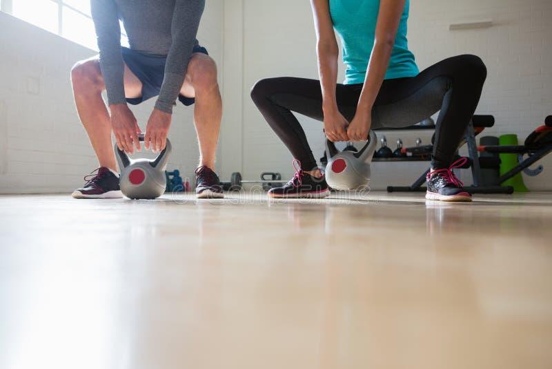 Низкий раздел спортсменов поднимая kettlebells стоковая фотография rf
