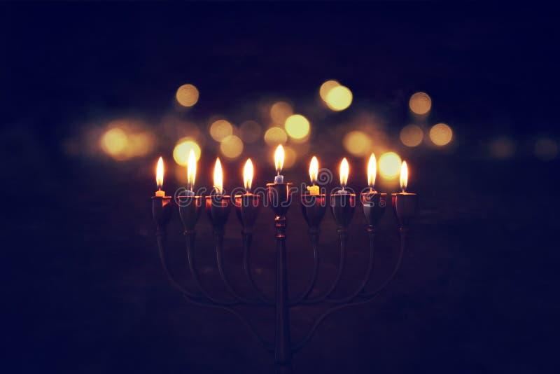 Низкое ключевое изображение еврейской предпосылки Хануки праздника с menorah & x28; традиционное candelabra& x29; и горя свечи стоковое изображение rf