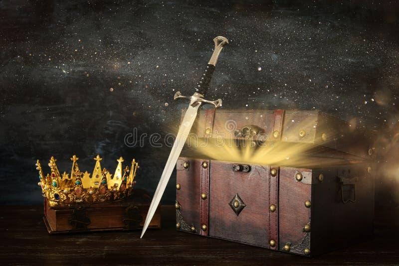 низкое ключевое изображение красивых ферзя/кроны короля над античной старой книгой, открытым комодом с сокровищем и шпагой период стоковые изображения