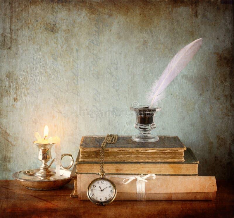 Низкое ключевое изображение белого пера, чернильницы и свечи на старом деревянном столе текстурированное изображение стоковое изображение