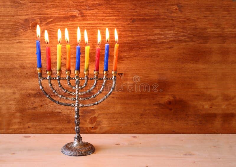 Низкое ключевое изображение еврейской предпосылки Хануки праздника с свечами menorah горящими над деревянной предпосылкой