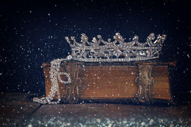 Низкое ключевое изображение декоративной кроны на старой книге Фильтрованный год сбора винограда стоковые изображения rf