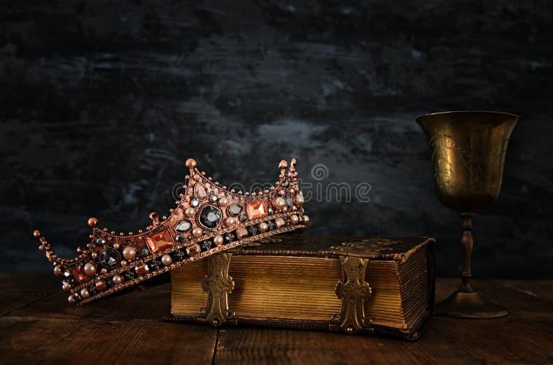 низкое ключевое изображение красивых ферзя/кроны короля на старой книге стоковые изображения rf