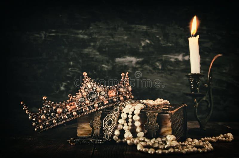 низкое ключевое изображение красивых ферзя/кроны короля на старой книге стоковое изображение
