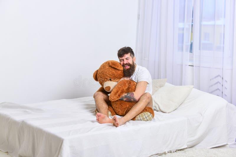 Никогда не вырастите вверх концепция Гай на счастливой стороне обнимает гигантский плюшевый медвежонка Мачо при борода и усик при стоковая фотография