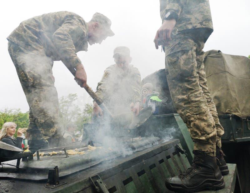 НИКОПОЛЬ, УКРАИНА - МАЙ 2019: Украинские войска варят кашу солдат и обрабатывают людей к ним на параде в честь стоковые фотографии rf