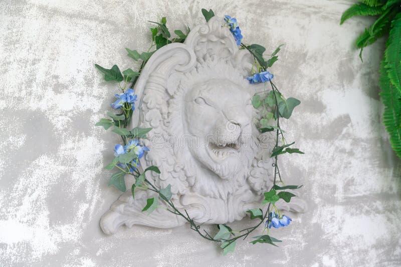 Новая статуя головы льва на стене цемента с плющом на студии бесплатная иллюстрация