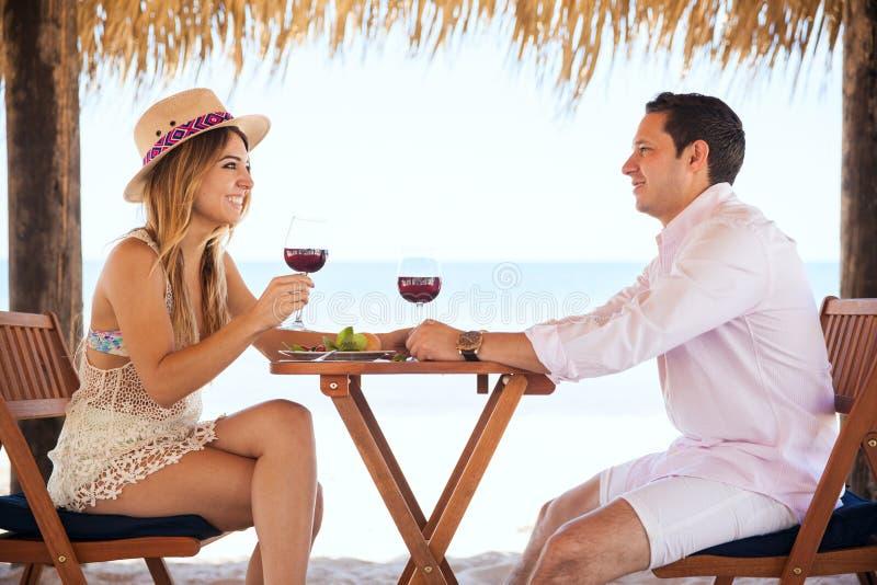 Новобрачные выпивая вино на пляже стоковое фото rf