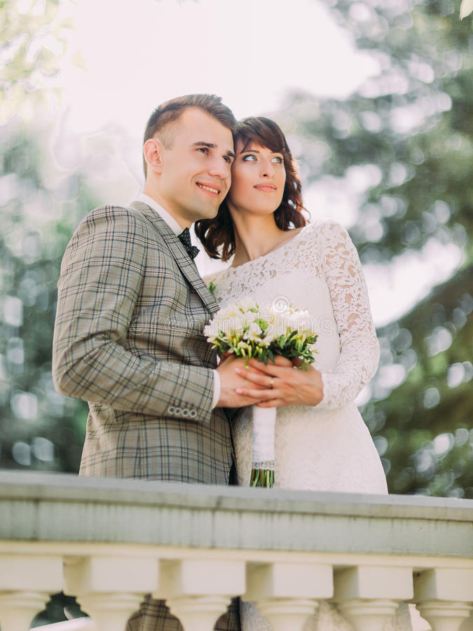 Новобрачные держат букет свадьбы и наслаждаются парком времени весной стоковые фото