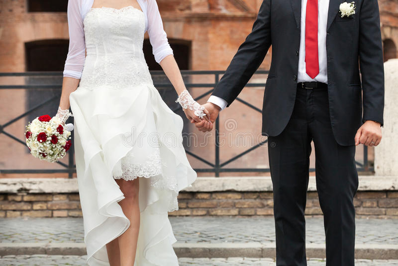 Новобрачные детализируют, рука об руку Город совместно гуляющ стоковое изображение rf