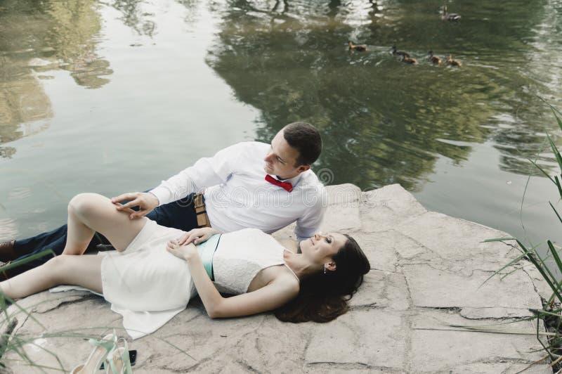 Новобрачные лежат на каменном близко озере с утками стоковая фотография rf