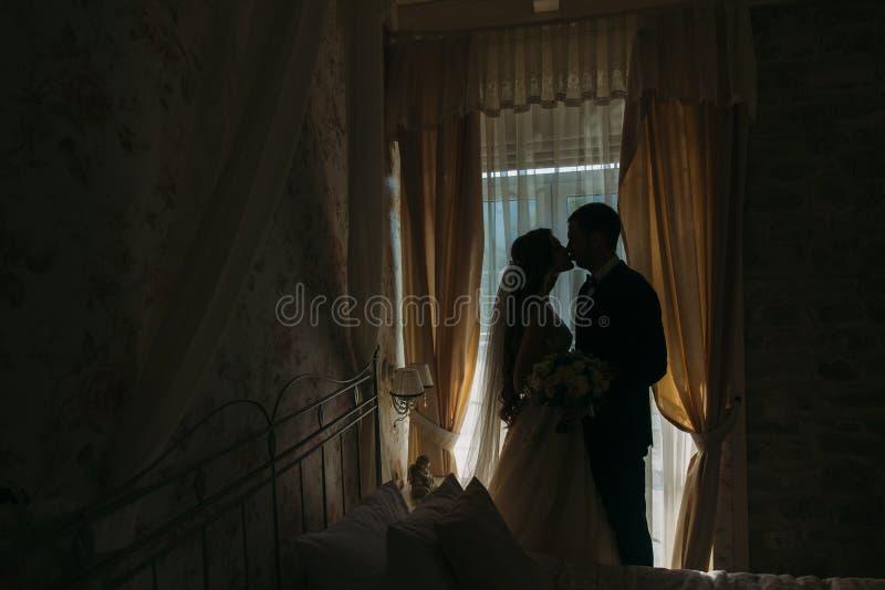 Новобрачные на дне свадьбы Счастливый роскошный жених и невеста стоя на свете окна в богатой комнате, нежном моменте стоковые изображения rf