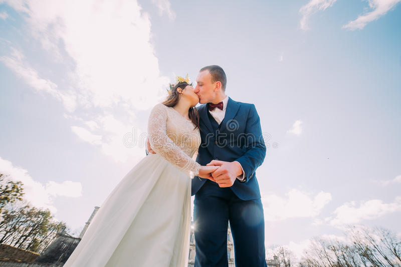Новобрачные Chherful целуя с изумительным голубым облачным небом как предпосылка Низкая угловая съемка стоковые фотографии rf