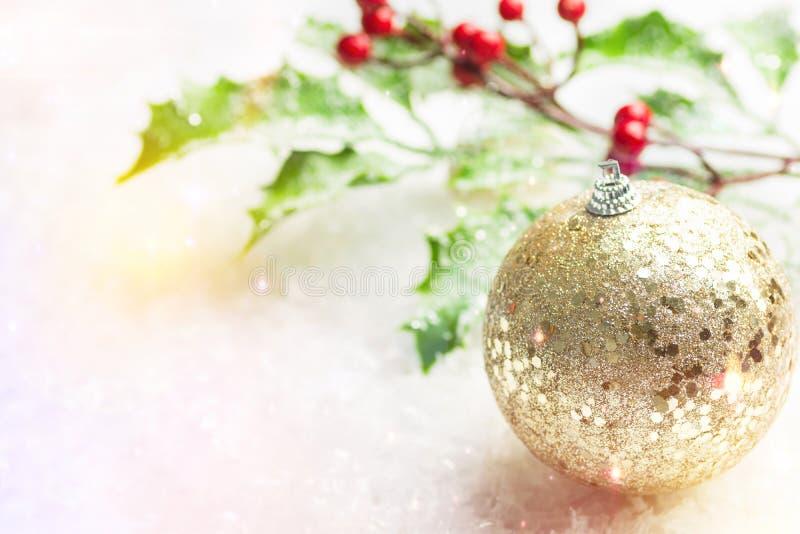 новогодние праздники поздравляют зимний лес золотой блестящий орнаментный шар голлиберри ветвь в снегу стоковые фото