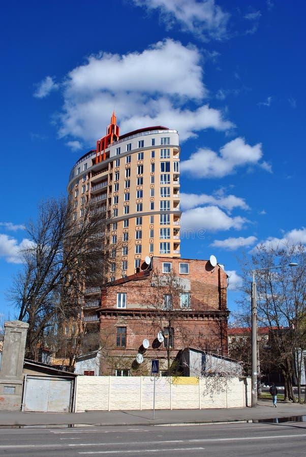 Новое высокорослое строение многоквартирного дома около малая старой от красного кирпича, голубого неба стоковые фотографии rf