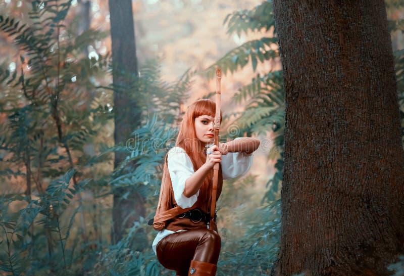 Новое изображение Робина Гуда как охотник девушки, привлекательная дама в белой рубашке и кожаных брюках вытянуло смычок перед съ стоковые изображения rf