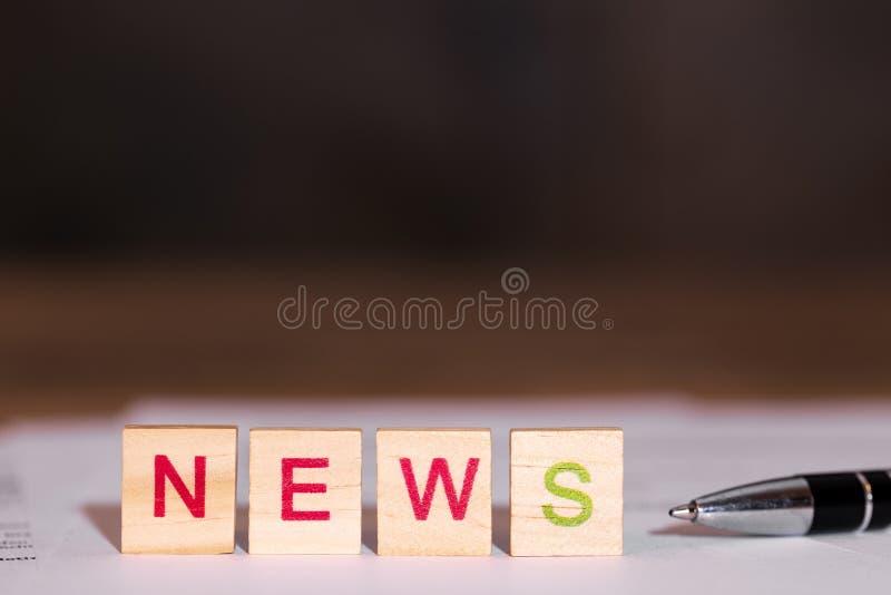 Новости на бумаге, ручка слова рядом с ей стоковые изображения rf