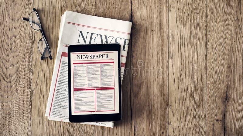Новости чтения на таблетке и газете на деревянной предпосылке стоковые фотографии rf