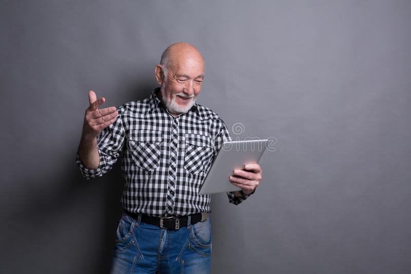 Новости чтения старшего человека на цифровой таблетке стоковое фото rf