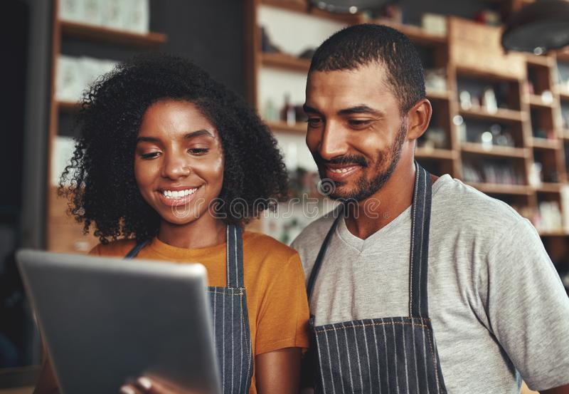 Новые владельцы бизнеса используя планшет в кафе стоковые фотографии rf