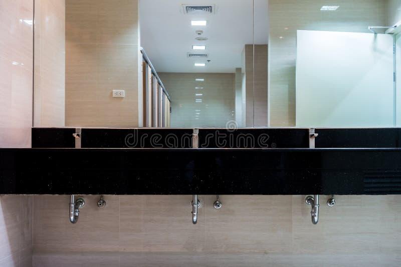 Новые зеркала и керамические washbasins счетчика гранита стоковое изображение