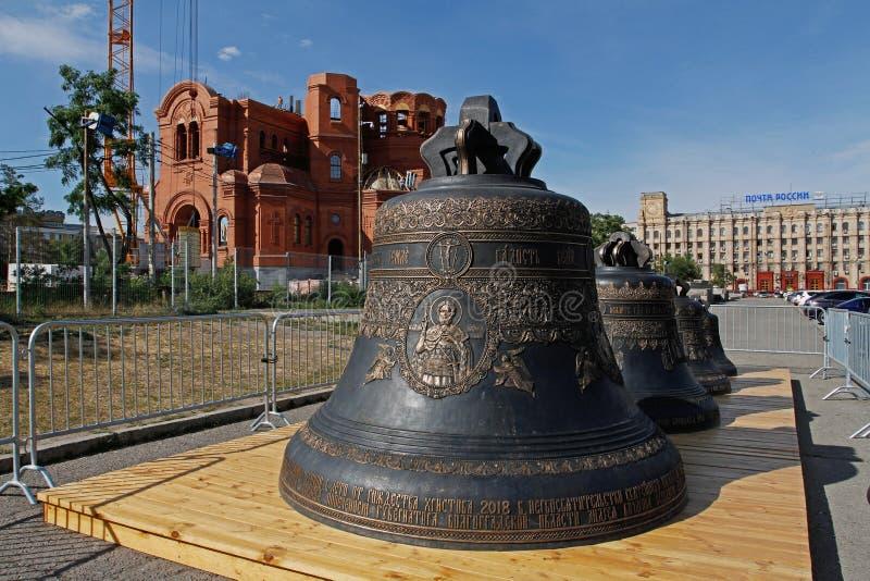Новые колоколы различных размеров стоят на деревянной платформе на фоне собора Nevsky под конструкцией в Volgo стоковое изображение rf