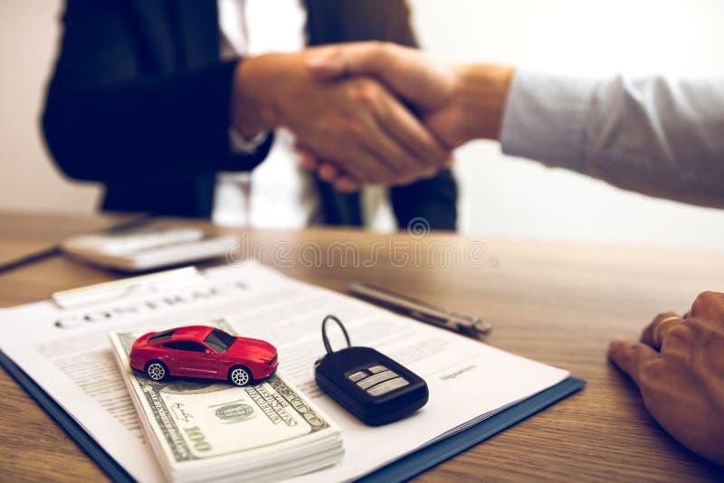 Новые покупатели автомобилей и продавцы автомобилей пожимают руки, чтобы заключить соглашения о продаже автомобилей стоковое изображение