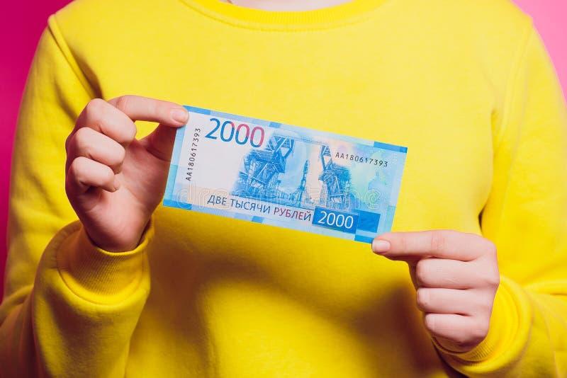 Новые русские бумажные деньги с Владивостоком отображают на ем 2000 рублей в руке женщины покрашенный свитер стоковое изображение rf